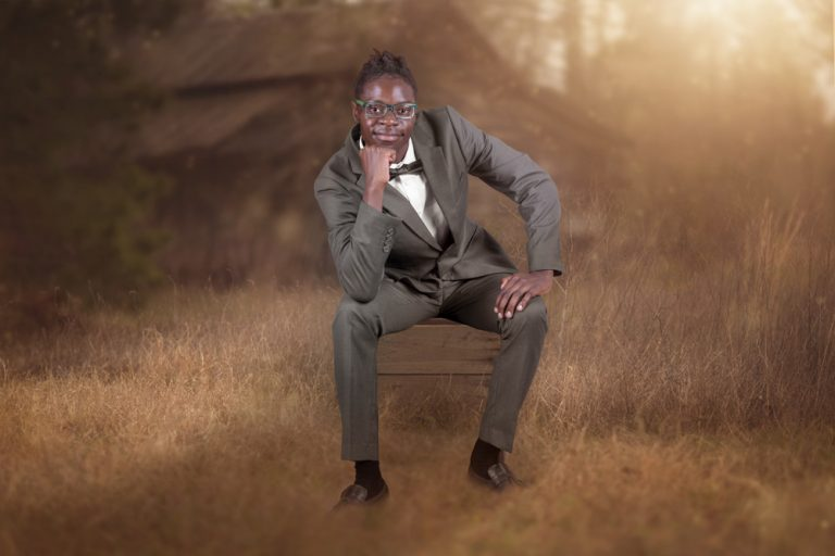 fine art portrait of an African man dressed in a suit sitting on a box in a field by katja photography