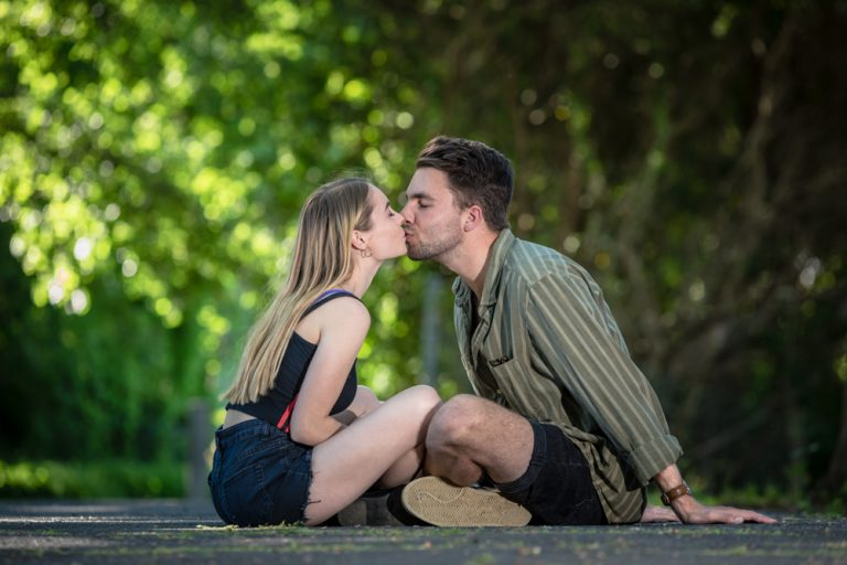 lifestyle portrait of young couple sitting and kissing by katja photography