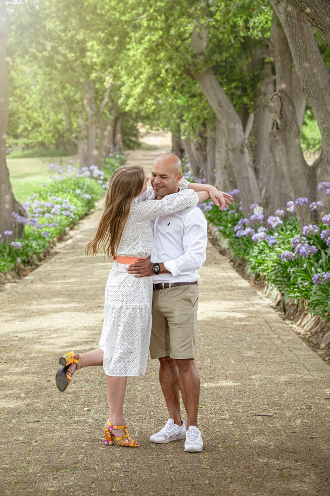 lifestyle portrait of couple in love standing in avenue of trees by katja photography