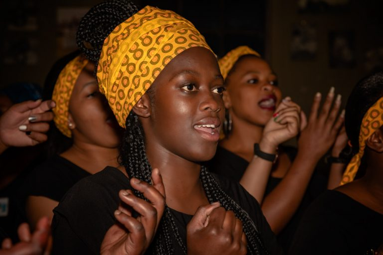 black young woman singing with yellow scarf wrapped around her head by katja photography events