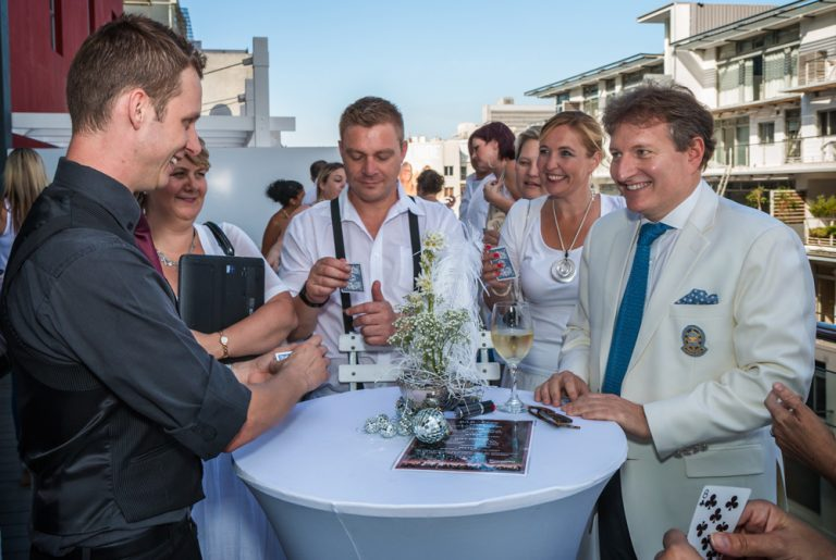 office party gathered around an outdoor table laughing by katja photography events