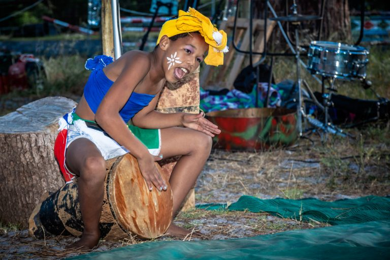 young black girl dressed in traditional wear playing on a drum by katja photography events