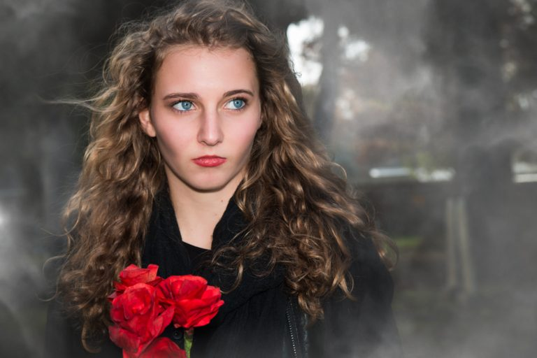 dramatic fine art portrait of a teen girl holding red flowers by katja photography