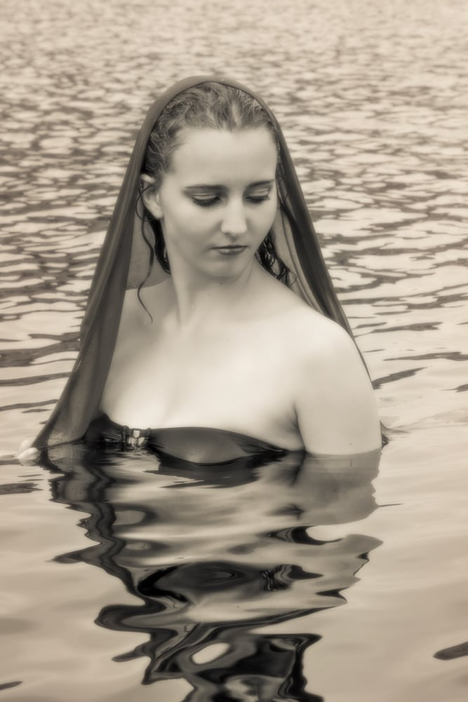 fine art portrait of young woman with veil standing in water by katja photography