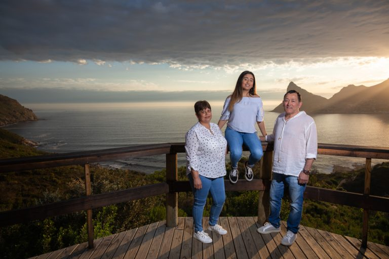 Lifestyle portrait of family on deck overlooking sea at sunset by katja photography