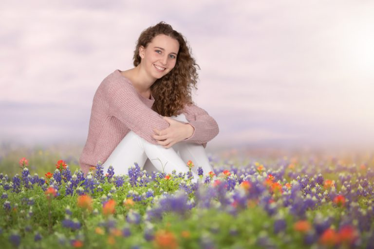 fine art portrait of a young woman sitting in a field of flowers by katja photography
