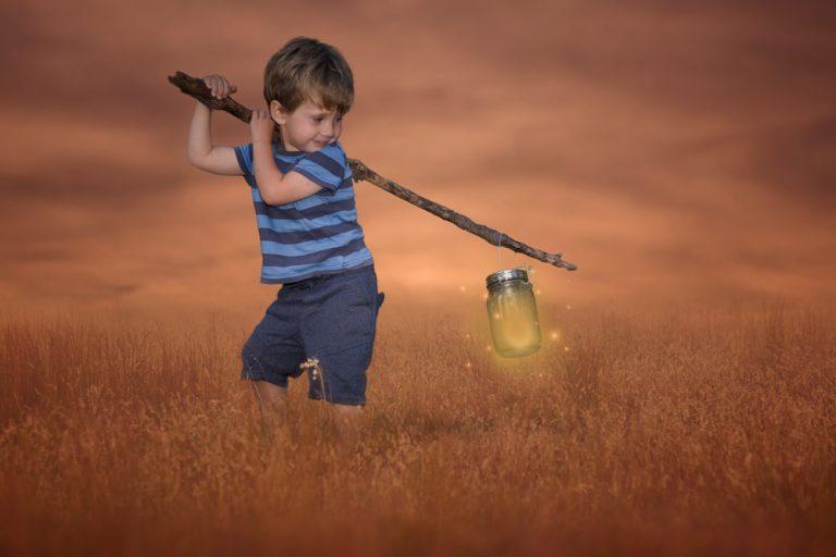 fine art portrait of a toddler boy carrying a lantern on a stick by katja photography