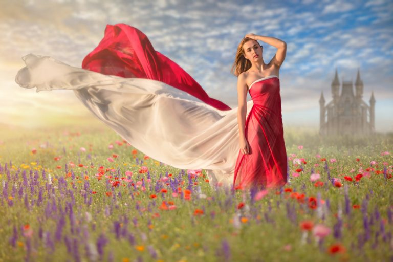fine art portrait of teen girl dressed in flowing red and white material standing in a flower field by katja photography