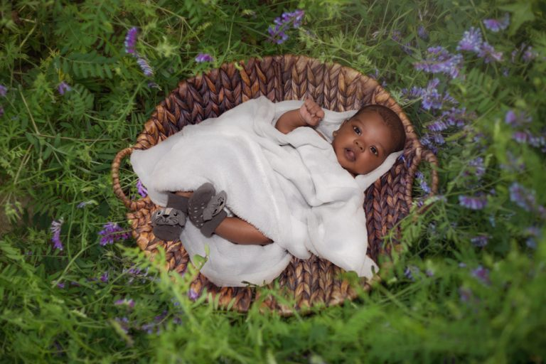 fine art portrait of a baby swaddled in white lying a basket by katja photography