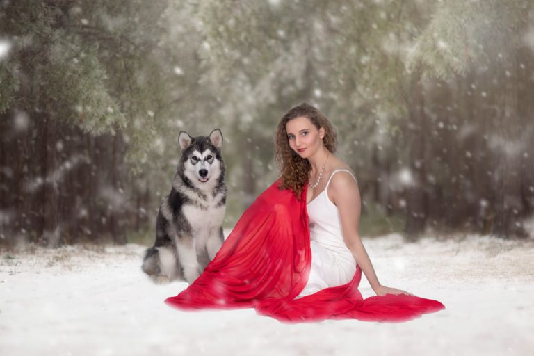 fine art portrait of teen girl sitting in the falling snow with malamute dog by katja photography