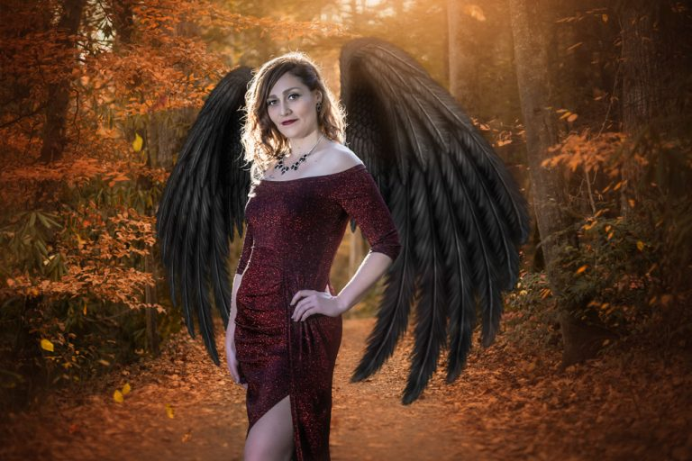 fine art portrait of a woman in red dress with black angel wings in autumn forest