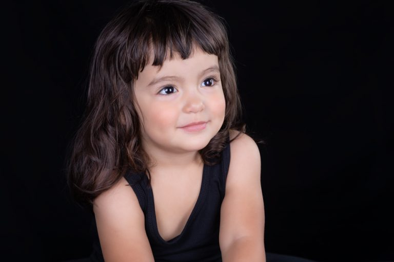studio portrait of toddler girl with black hair against a black background by katja photography